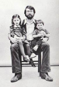 Black and white photo of Mike Gauldin seated with his children Amanda and Patrick.