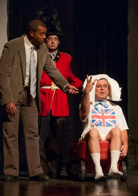 Justin Stewart interviews the new-born royal baby, played by David Spear, while a royal sentry played by Ben Pollock stands guard.