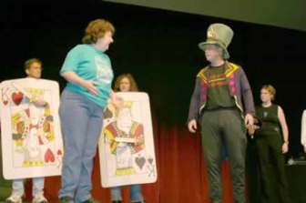 Katherine Shurlds and Charlie Alison as the Mad Hatter. In the background are Kyle and Laura Kellams as the cards and Sarah Warnock as part of the chorus.