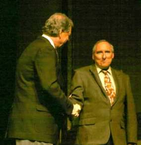 Grady Jim Robinson as Bill Clinton shakes hands with Al Gore, played by Rusty Garrett.