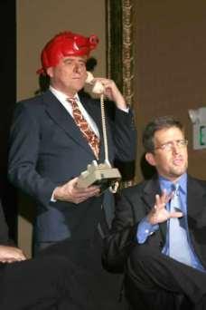 Rusty Garrett as Frank Broyles on the line and Kyle Kellams as Regis Philbin.